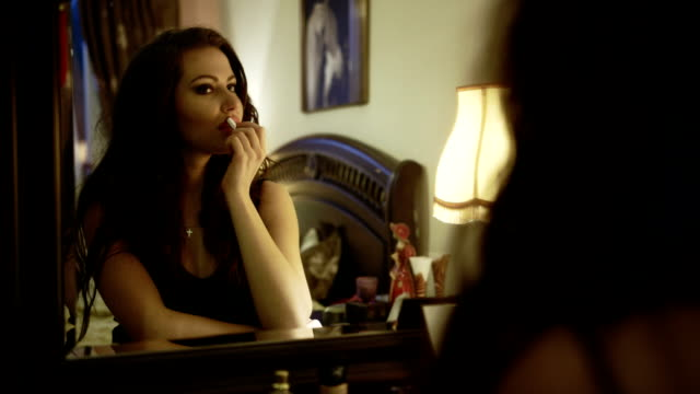 Young beautiful woman applying lipstick sitting in front of a big mirror. video
