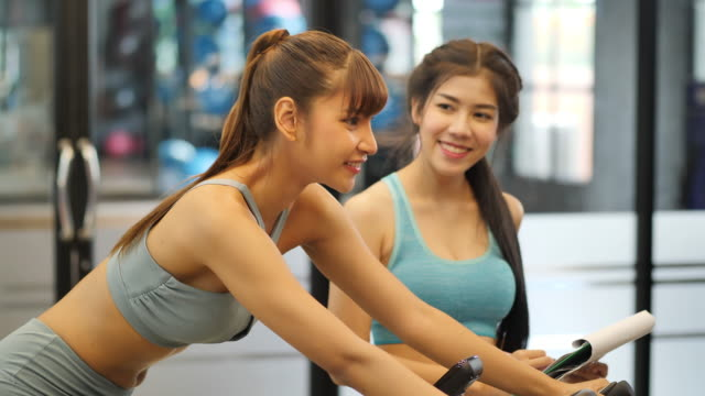 Young Beautiful Woman Asian Exercising With Exercise Bike And Trainer  Helped Guide In Gym Fitness And Healthy Lifestyle Concept Side View Of Girl  In Sportswear Slow Motion Stock Video - Download Video