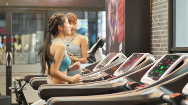 Young beautiful woman asian running on a treadmill and trainer helped guide at gym. Fitness and healthy lifestyle concept. Side view of girl in sportswear jogging exercise. real time