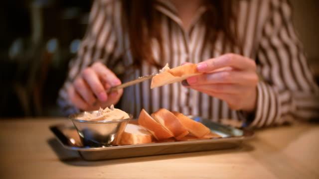 아름 다운 젊은 여성 갈색 카페에 빵 한 조각에 페이트를 얼룩. 칼으로 근접 여자의 손입니다. - 식빵 한 덩어리 스톡 비디오 및 b-롤 화면