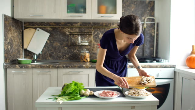 Young beautiful woman cook cutting the mushrooms on wooden board for pizza in the kitchen at home video