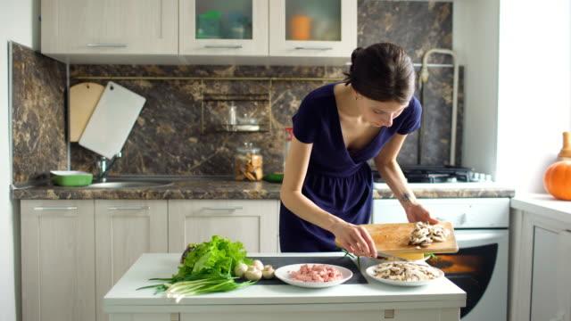 ung vacker kvinna skära svampen på trä ombord för pizza i köket hemma - endast vuxna bildbanksvideor och videomaterial från bakom kulisserna