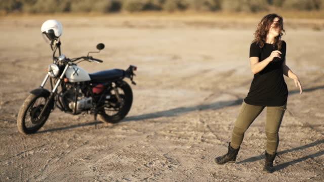 年輕漂亮的女人在日出或日落時在沙漠中跳舞,然後坐在一輛摩托車和騎走了。 - {{asset.href}} 個影片檔及 b 捲影像