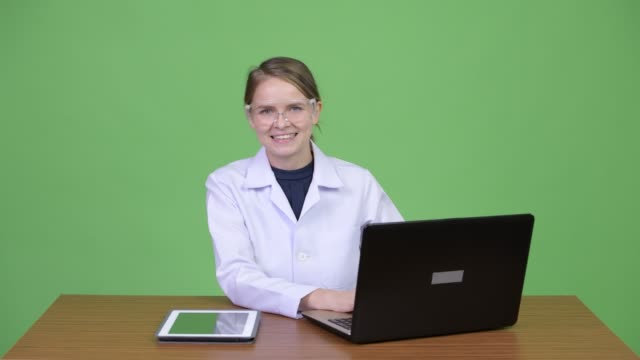 Young beautiful woman doctor with protective glasses sitting behind desk