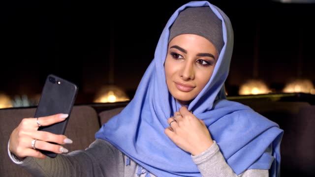 young beautiful woman doing selfie on mobile phone camera - abbigliamento religioso video stock e b–roll