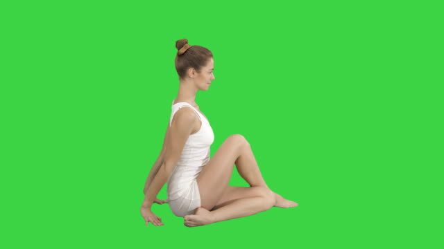 Young beautiful woman doing yoga asana Marichyasana on a Green Screen, Chroma Key