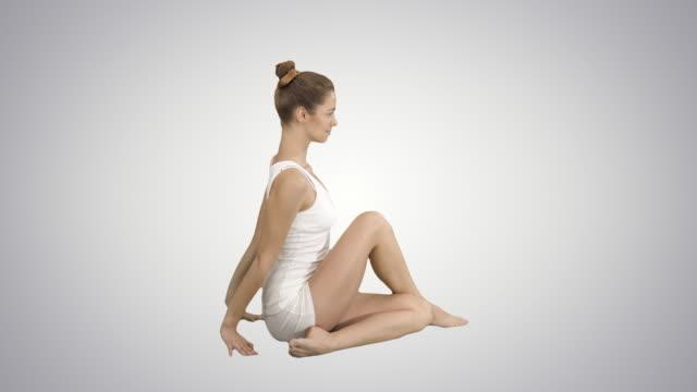 Young beautiful woman doing yoga asana Marichyasana on gradient background