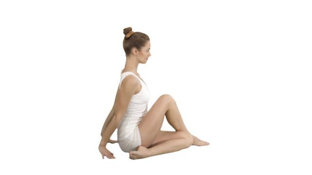 Young beautiful woman doing yoga asana Marichyasana on white background