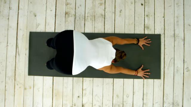 Young beautiful woman doing yoga exercise, sun salutation pose video