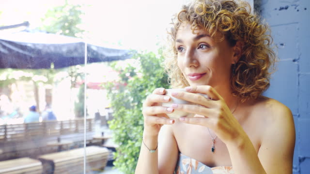 Young beautiful woman enjoying her coffee. video