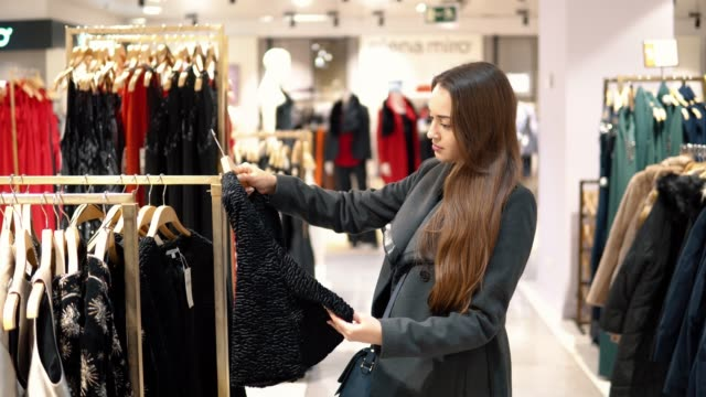 young beautiful woman finding herself new clothes in a store supermarket 4k shot of a young beautiful woman finding herself new clothes in a store supermarket shop clothing stock videos & royalty-free footage