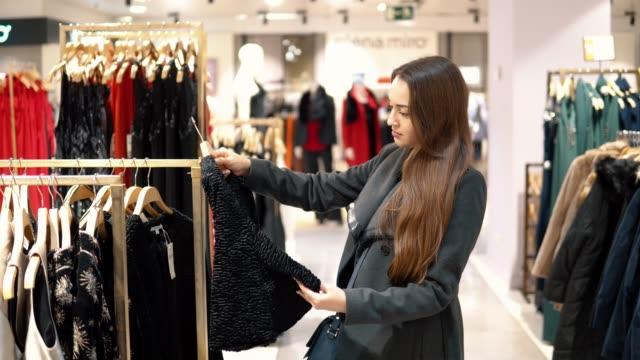 vídeos de stock, filmes e b-roll de jovem bela mulher encontrar-se novas roupas em um loja de supermercado - vestuário
