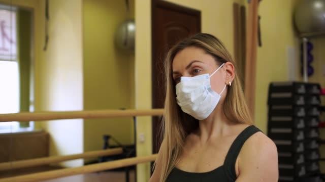 stockvideo's en b-roll-footage met de jonge mooie bus van de de vrouwengeschiktheidstrainer traint bicepsspieren oefening met rode halter die medisch beschermend masker tijdens coronavirus covid-19 quarantaine draagt - mirror mask