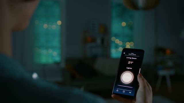 Young Beautiful Woman Gives a Voice Command to a Smart Home Application on Her Smartphone and Lights in the Room are Being Turned On. She Walks and Sits on a Couch. It's a Cozy Evening. Young Beautiful Woman Gives a Voice Command to a Smart Home Application on Her Smartphone and Lights in the Room are Being Turned On. She Walks and Sits on a Couch. It's a Cozy Evening. Shot on RED EPIC-W 8K Helium Cinema Camera. electrical equipment stock videos & royalty-free footage