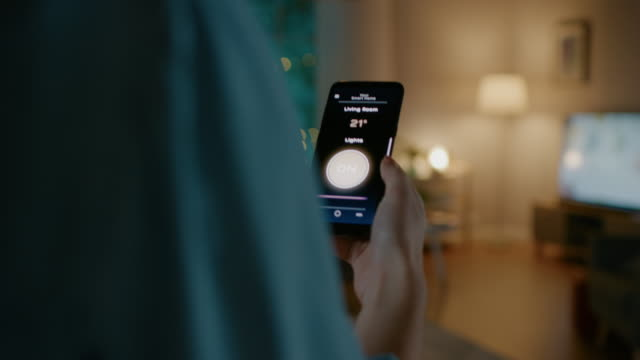 若い美しい女性は彼女のスマートフォン上のスマートホームアプリケーションに音声コマンドを与え、部屋の照明がオンにされています。彼女は歩いてソファーに座っています。居心地のよ� - モノのインターネット点の映像素材/bロール
