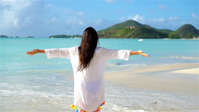 Young beautiful woman having fun on tropical seashore. Happy girl walking at white sand tropical beach. SLOW MOTION video