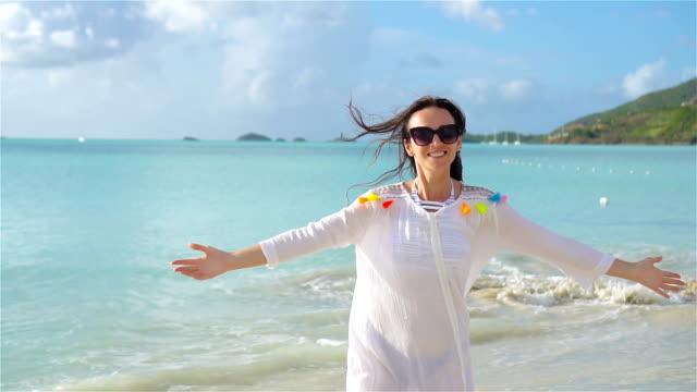熱帯の海岸上で楽しんで若い美しい女性。熱帯の白砂のビーチを歩いて幸せな女の子。スローモーション ビデオ