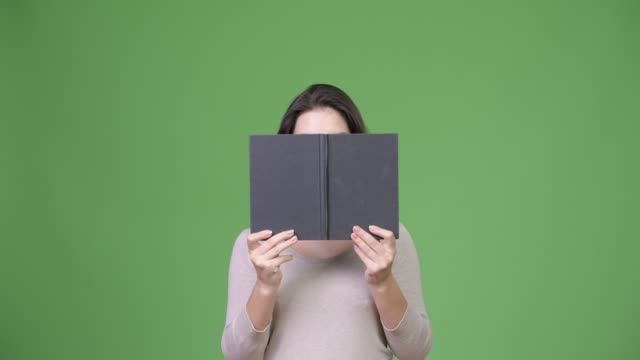 young beautiful woman hiding behind book - donna si nasconde video stock e b–roll