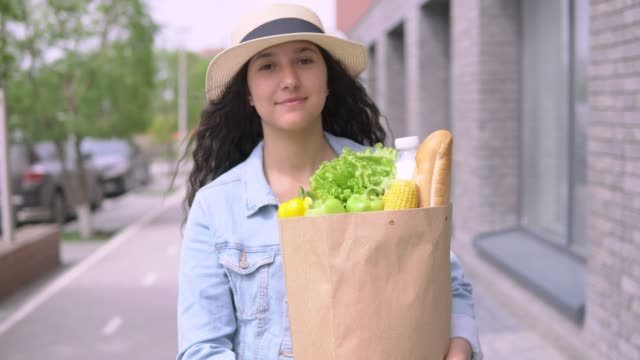 Young beautiful woman in a denim jacket and hat carries a grocery bag. 4K video