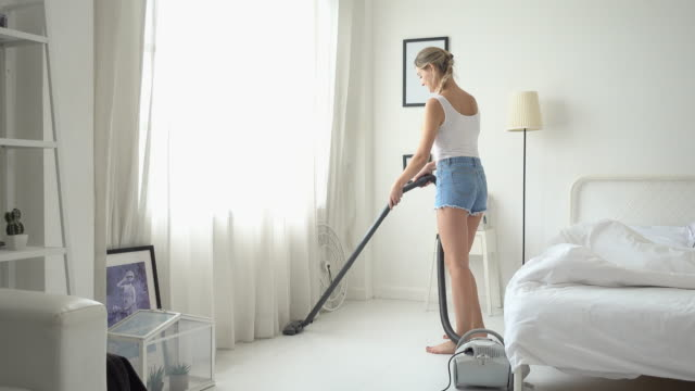 Young Beautiful Woman in Casual Shirt and Shorts Vacuum Cleaning at her room Young Beautiful Woman in Casual Shirt and Shorts Vacuum Cleaning at her room cordless phone stock videos & royalty-free footage