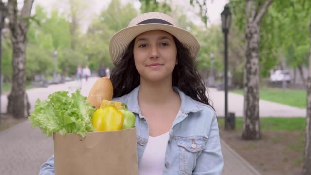 A young beautiful woman in good mood walks down the street in a city park and carries a large grocery bag. video