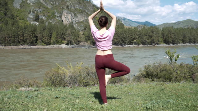 young beautiful woman in red tank top practicing outdoors, doing bending tree posture, variation of vrksasana, in park on summer day. altai, the river katun. - posizione corretta video stock e b–roll