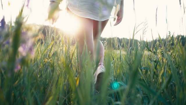young beautiful woman in sneakers and shorts walking on meadow with green grass nature slow motion video. girl in the field legs at sunset close-up on the grass sunlight lifestyle silhouette - бунтарство стоковые видео и кадры b-roll