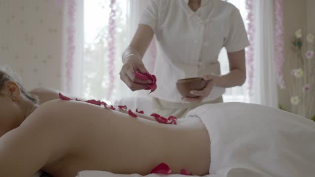 giovane bella donna nel salone di massaggio spa. rilassa il trattamento con odore di fiori di rose. - dorso umano video stock e b–roll