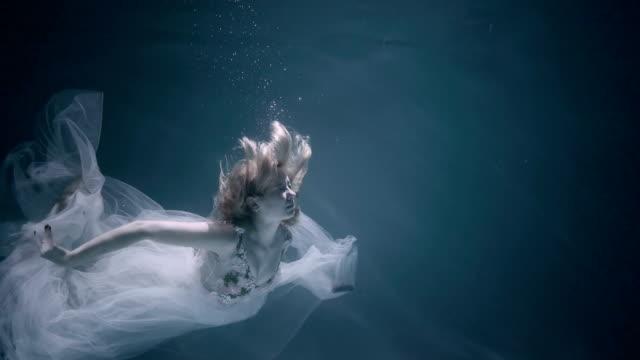 stockvideo's en b-roll-footage met mooie jongedame in witte jurk onderwater zwemmen - ocean under water