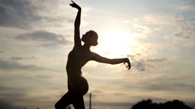 若くてきれいな女性が砂漠で日の出のボディー スーツを身に着けているを踊ってください。 - バレエ点の映像素材/bロール