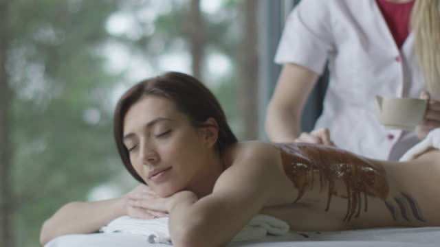 Young beautiful woman is getting a relaxing chocolate massage treatment in wellness center. video