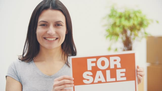 Young beautiful woman is holding a plate with words FOR SALE written on it, offering house for sale and moving out.