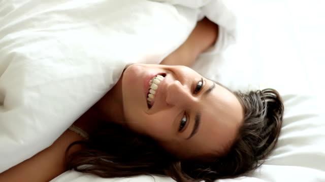 młoda piękna kobieta wygląda w obejmuje w łóżku - kołdra filmów i materiałów b-roll