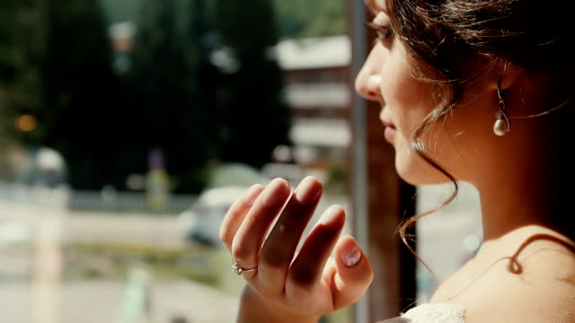 Young, beautiful woman looks through the window . video