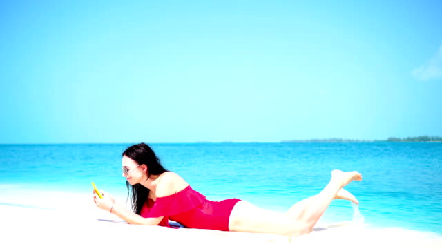 Young beautiful woman lying at shallow tropical water - vídeo