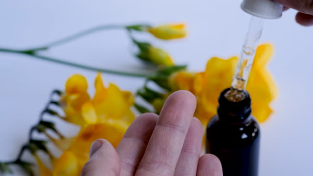 Young beautiful woman make drop of hyaluronic acid or cosmetic serum on her finger. Young beautiful woman make a drop of hyaluronic acid or cosmetic serum on her finger. Close up of dark glass bottle with essential oil and yellow spring flowers on white background. Skincare concept. serum sample stock videos & royalty-free footage