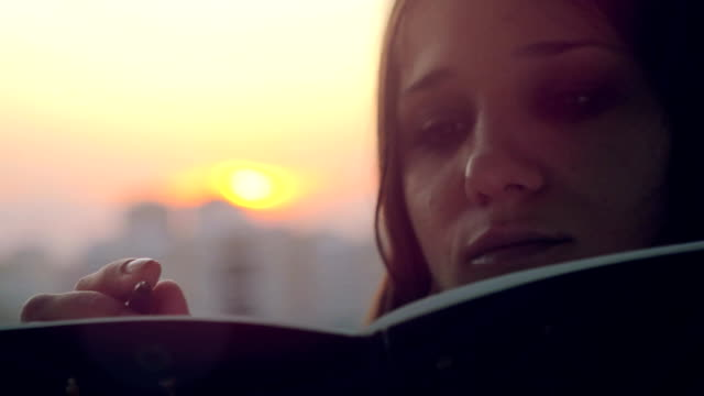 Young beautiful woman making some important notes on notebook at sunset in the city video
