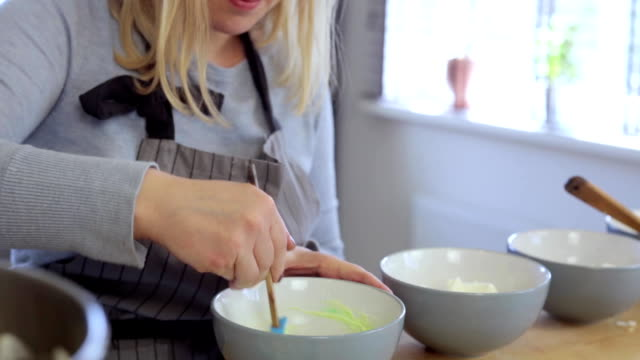 Young beautiful woman making the colored cream for desserts, mixing ingredients in a bowl. Female cooking in the kitchen video
