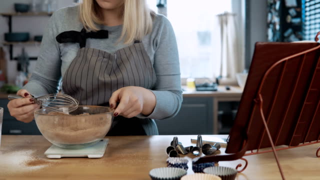 Young beautiful woman mixing ingredients in bowl, using whisk. Attractive female looking at recipe from cooking book video