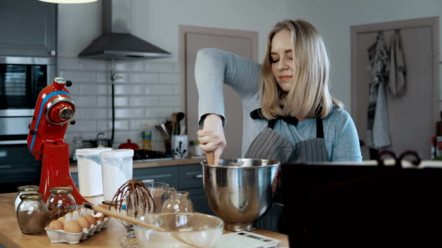 Young beautiful woman mixing the ingredients in a bowl, preparing dough for baking. Blonde female in kitchen video