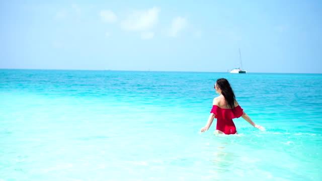 Mujer hermosa joven en la playa. Chica feliz disfrutar de su exótica isla tropical vacaciones - vídeo