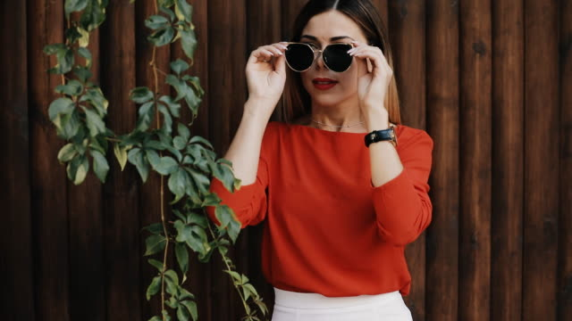 Young beautiful woman portrait in sunglasses near wooden wall look time at watch Young beautiful woman portrait in sunglasses near wooden wall look time at watch saturated color stock videos & royalty-free footage
