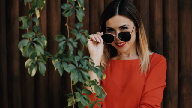 Young beautiful woman portrait in sunglasses near wooden wall Young beautiful woman portrait in sunglasses near wooden wall saturated color stock videos & royalty-free footage
