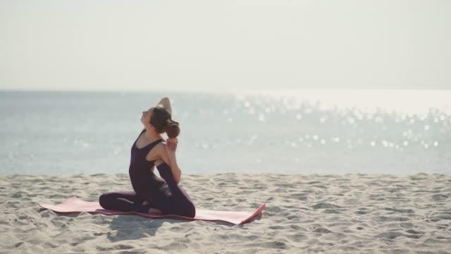 若い美しい女性の晴れた日にビーチでヨガの練習します。健康的なアクティブなライフ スタイル コンセプト - ヨガ点の映像素材/bロール