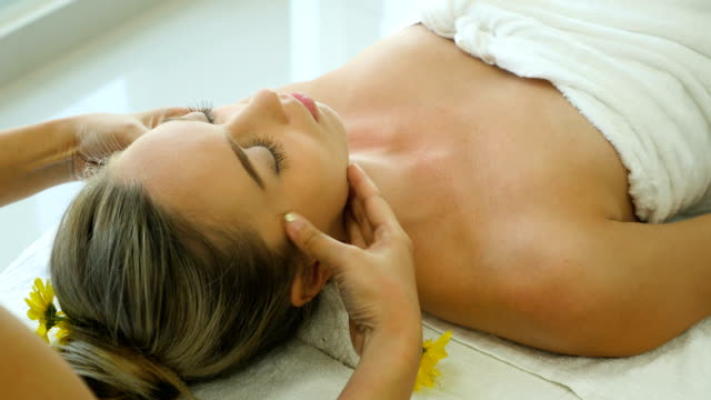 young beautiful woman relaxing in spa salon and receiving head or face massage - spa stock videos & royalty-free footage