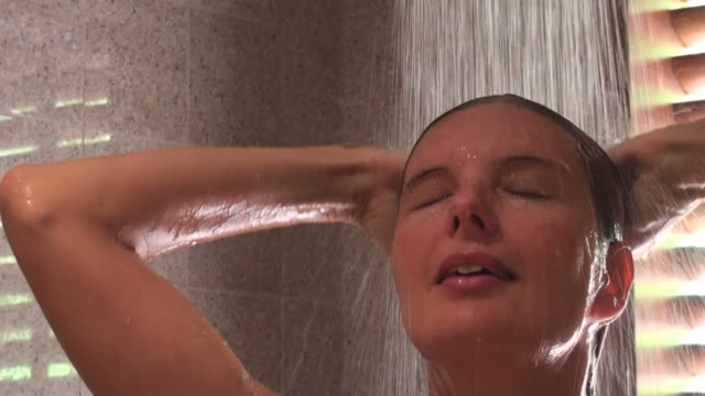 Young beautiful woman relaxing while taking her shower video