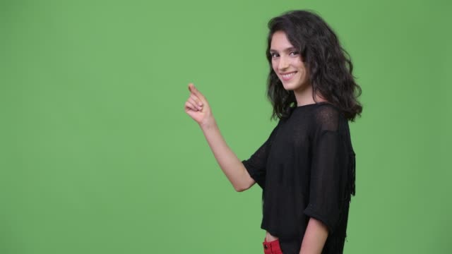 Young beautiful woman showing something Studio shot of young beautiful woman against chroma key with green background snapping stock videos & royalty-free footage