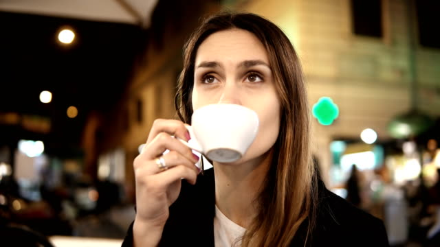 Young beautiful woman sitting in the city centre in cafe, holding cup and drinking coffee in the evening alone video