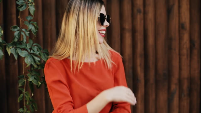 Young beautiful woman smiling and laughing near wooden wall Young beautiful woman smiling and laughing near wooden wall saturated color stock videos & royalty-free footage