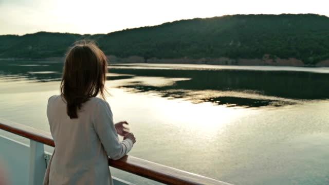 stockvideo's en b-roll-footage met jonge mooie vrouw staande op het dek van het cruiseschip en kijken naar de rivier. - cruise